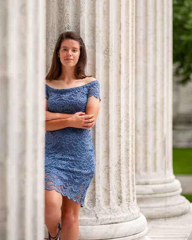 Outdoor portrait photography shot of a young woman standing among columns in front of a large building.
